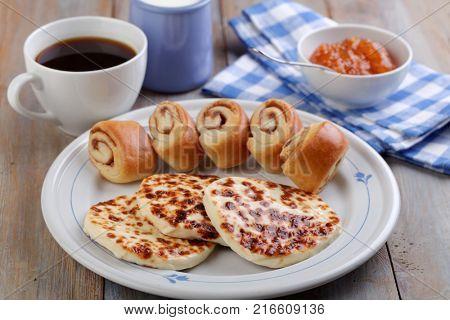 Finnish breakfast with squeaky cheese Leipajuusto, mini cinnamon buns, cloudberry jam, and black coffee