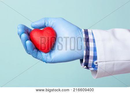 Doctor holding a red heart in his hand