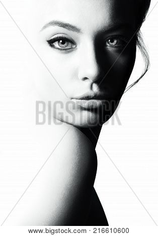 High contrast black and white portrait of a beautiful girl. Femininity and beauty, free space for your text.