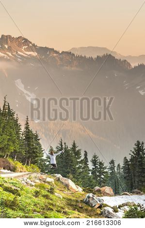 Woman Leaps Alongside Trail in Rainier National Park