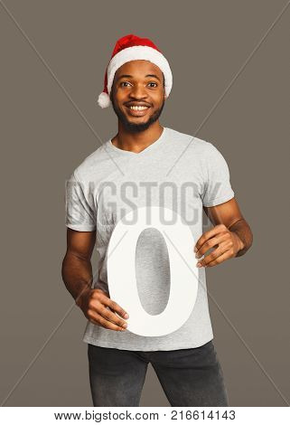 Happy black man with 0 number portrait. African-american boy in santa hat at studio background. One of shots to compose 2018 for new year and christmas greeting card