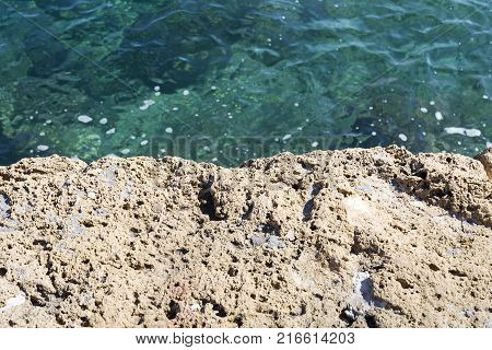 A stone slab near the sea. The texture of the water and stone. The weather is nice.