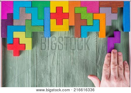 Concept of decision making process logical thinking. Logical tasks. Conundrum find the missing piece of the proposed. Hand holding puzzle element. Background with colorful shapes wooden blocks