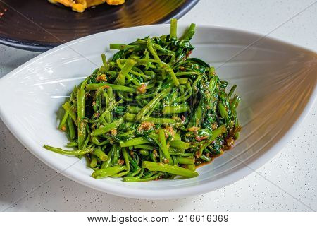 Chinese Fried Water Spinach with spicy chili garlic and soy sauce on white plate in Singapore called Sambal Kangkong