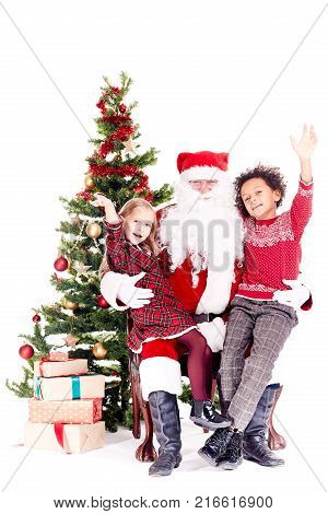 Santa Claus sitting in chair near Christmas tree with multi-ethnic boy and girl on his lap