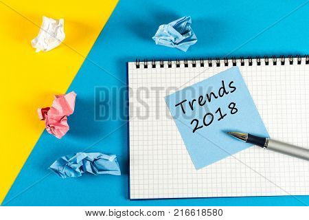 Trends 2018. what to expect from next year. Memo at yellow and blue background with notepad. Mockup with empty space for text.