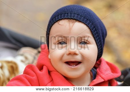 closeup portrait of smiling little girl with only two teeth. Baby girl laughing. Happy childhood, one year old child, autumn season, outdoors concept