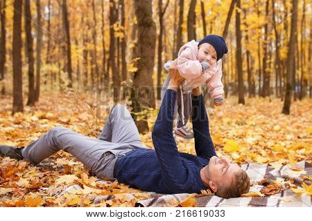 young laughing father play with a little daughter in autumn park. Dad holding baby girl in hands. Happy family, paternal love, autumn season, outdoors concept