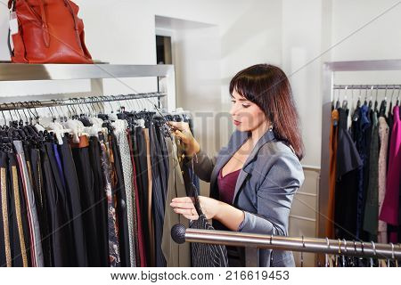 professional stylist woman chooses clothes in the store. Shopper near clothes rack in fashion boutique. Shopping concept