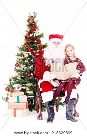 Santa Claus reading a book for cute little girl sitting on his lap near Christmas tree