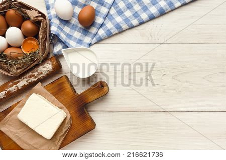 Cooking ingredients for sweet cookies background. Eggs, milk flour, butter and kitchen utensils on white wood table. Recipe or baking classes mockup, pastry making concept, top view, copy space