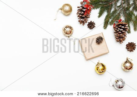 Christmas balls, gift box with fir tree and conifer cone on wood background, top view. Copy space.