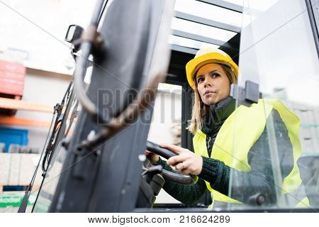 Female forklift truck driver in an industrial area. A woman sitting in the fork lift outside a warehouse.