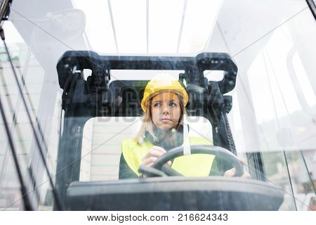 Female forklift truck driver in an industrial area. A woman sitting in the fork lift outside a warehouse. Shot through glass.