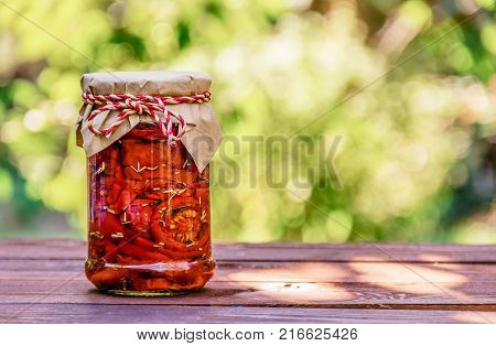 Sun dried tomatoes in glass jar on wooden table. Delicious gift. Vegetarian food. Copy space