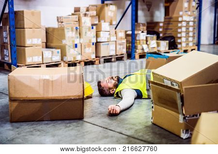 An accident in a warehouse. Man lying on the floor among boxes, unconscious.