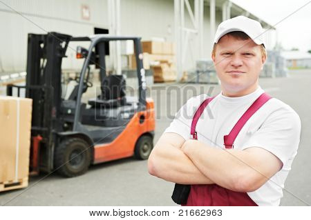young cheerful warehouse worker driver in uniform in front of forklift stacker loader