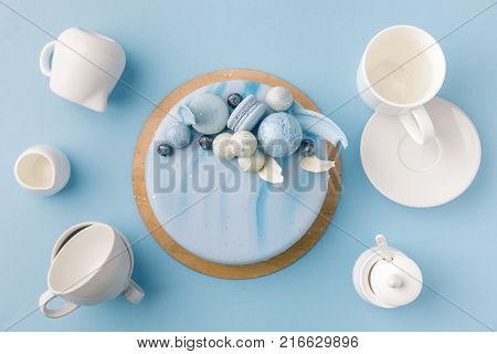 top view of blue cake surrounded by flatware isolated on blue