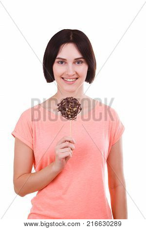 Beautiful brunette girl with a smile holds a frozen chocolate on a stick on a white isolated background. Front view