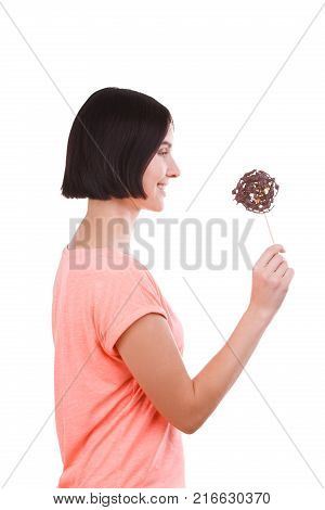 Beautiful girl with a smile in a pink t-shirt looks at the frozen chocolate on a stick on a white isolated background. Side view