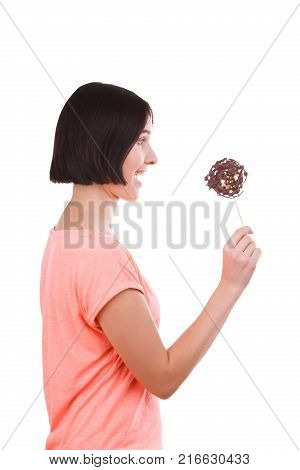 Young brunette girl in pink t-shirt surprised holds a frozen chocolate on stick isolated on white background. Side view