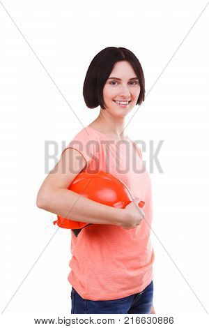 Beautiful brunette girl in pink t-shirt with smile stands sideways and holds a hard hat against white isolated background