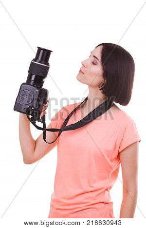 Young photographer girl in pink t-shirt examines camera at not on white isolated background
