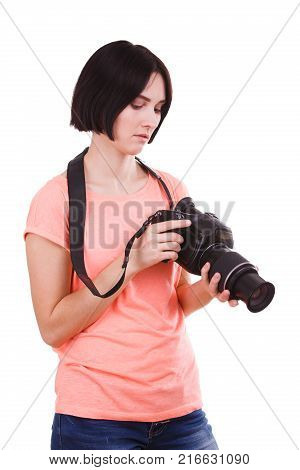 A beautiful, young girl in a pink t-shirt examines the panel on the camera in her hands on a white isolated background