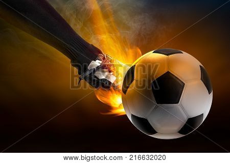Strength of athlete to kicking the soccer ball with power fire blaze in dark background