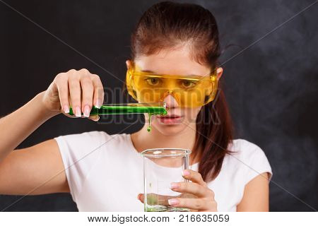 The girl the laboratory assistant young, in a white tank top, in glasses. Pouring green liquid from a test tube into a test tube into a flask close-up on a black background