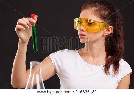 A lab assistant in glasses and a white T-shirt is holding a closed test-tube with a green liquid on a black background