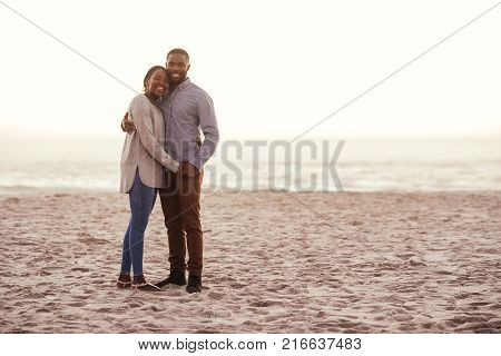 Smiling young African couple standing arm in arm together on a sandy beach while enjoying a sunset