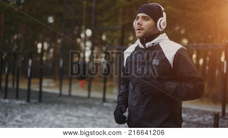 Attractive man in headphones doing warm-up exercise preparing for jogging while listening music in winter park outdoors