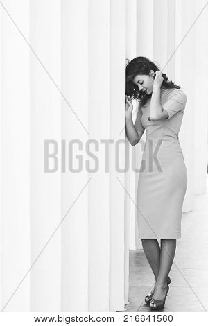 tenderness beautiful woman in a dress poses near ancient colons