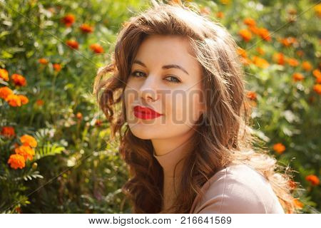 portrait of beauty smiling woman poses on background bed of flowers