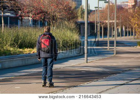 Happy man roller blading in public city park