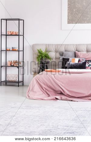Copper plate and pink bedclothes on king-size bed in stylish minimalist loft interior with decorative metallic items on black rack