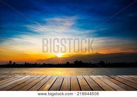 Wooden walkway at riverside on beautiful sunset background