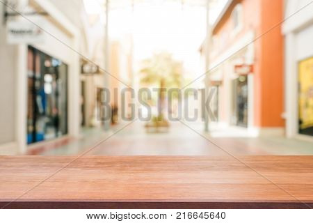 Wooden board empty table blurred shopping mall background. Perspective brown wooden table blur in department store background - can be used for display or montage your products. Mock up for of product