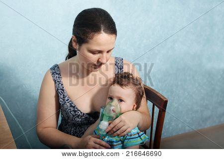 Two Year Old Baby Girl Inhaling From The Inhaler, Her Mother Holding Her In The Arms And Comforting
