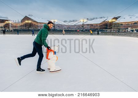 Outdoor Shot Of Glad Bearded Male Wears Green Jacket And Hat, Stands Near Skate Aid As Trying To Obt