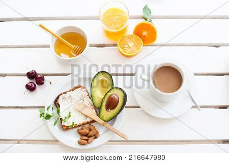 Table set for a typical breakfast with orange juice toast avocado and coffee