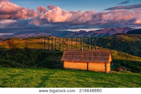 Shed On The Grassy Hillside In Red Evening Light