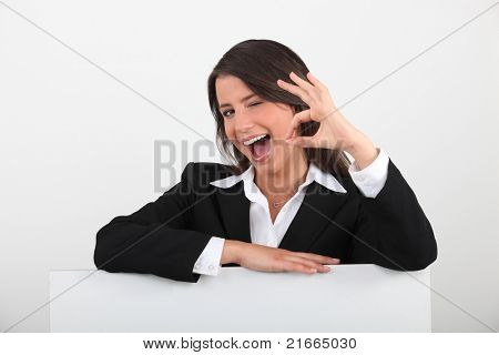 Cheeky young woman in a suit giving the OK sign with a blank board ready for text