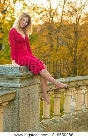Beautiful Young Woman in red dress and old arhitecture on Fall Nature Background