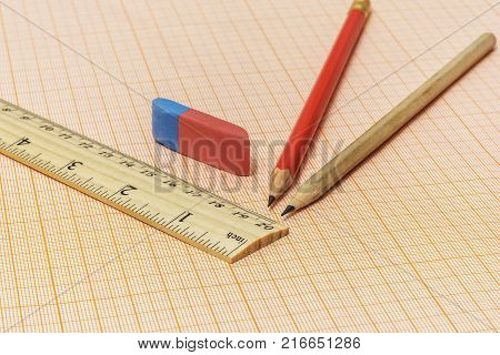 On a millimeter paper there is a wooden ruler an eraser and two simple pencils