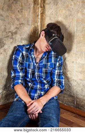 Young Man sleeping in Virtual Reality Glasses by the Old Wall in the Derelict House