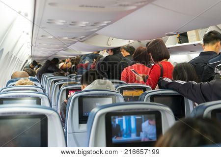 Los Angeles USA 12 2017: People are standing and sitting in an airplane cabin before disembarking. Interior of airplane with passengers getting off at Los Angeles California.