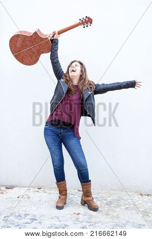 Portrait of happy young  woman raising guitar over head in triumph. Creative or success concept