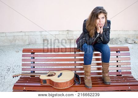 Pensive female street guitar player sitting on bench and waiting busy hour to start playing. Creative work concept